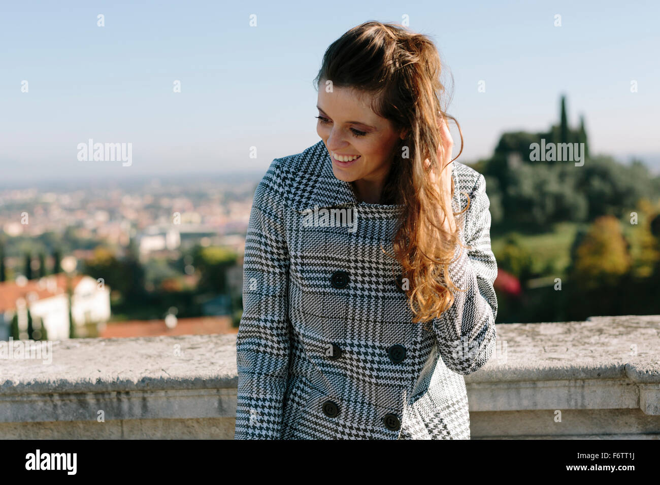 Italy, Vicenza, smiling brunette woman in checkered coat - Stock Image
