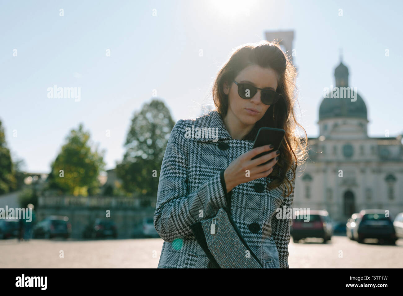Italy, Vicenza, woman wearing checkered coat and sunglasses looking at cell phone - Stock Image