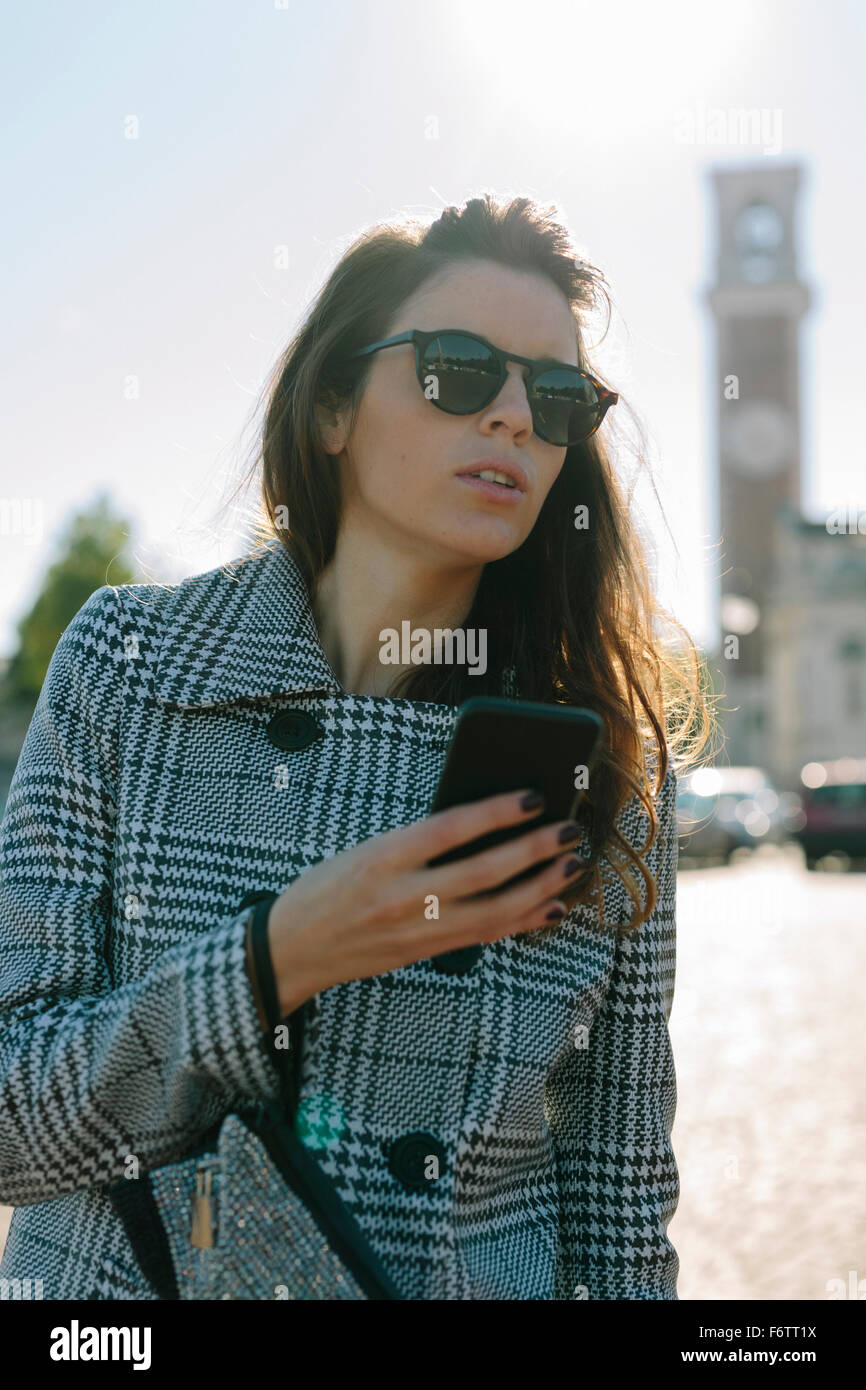 Italy, Vicenza, woman wearing checkered coat and sunglasses holding cell phone - Stock Image