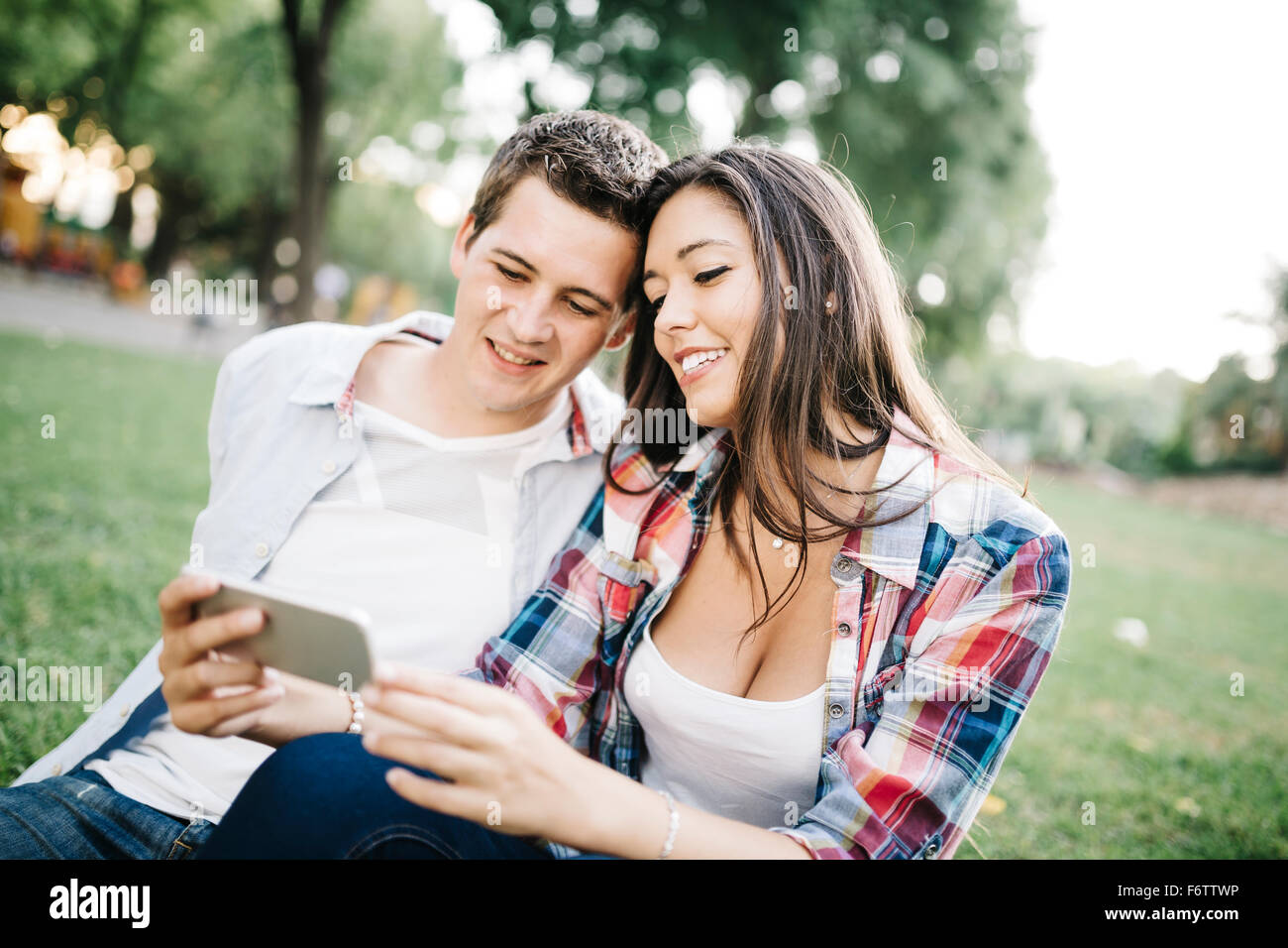 Portrait of young couple in love watching something on smartphone in a park - Stock Image