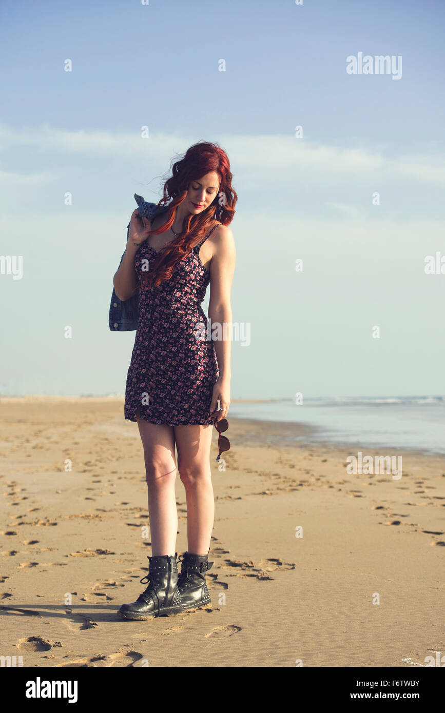 Spain, El Puerto de Santa Maria, portrait of redheaded young woman standing on the beach - Stock Image