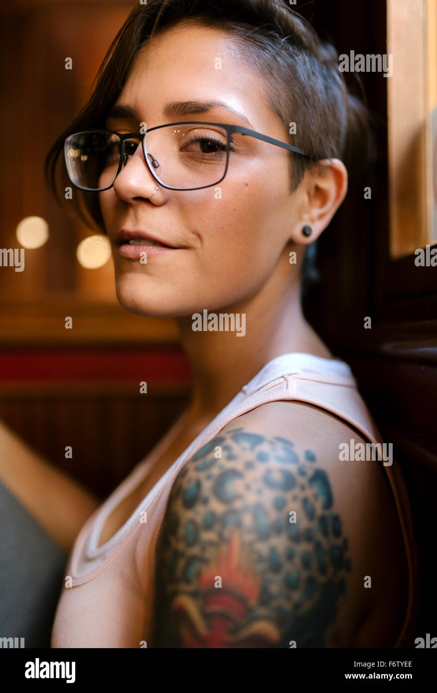 Portrait Of Tattooed Young Woman With Nose Piercing Wearing
