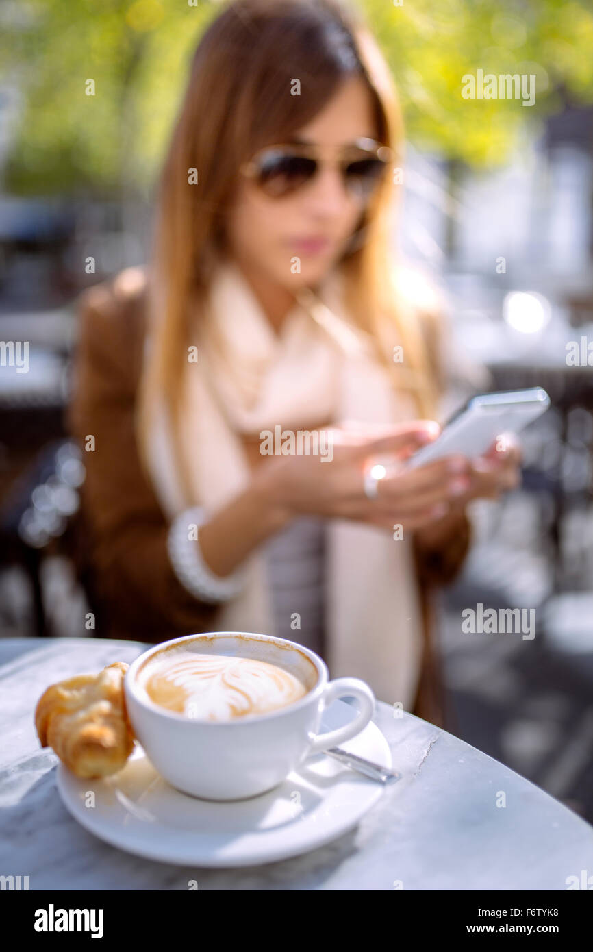 Spain, Gijon, Cup of cappucino, young woman in background using smart phone - Stock Image