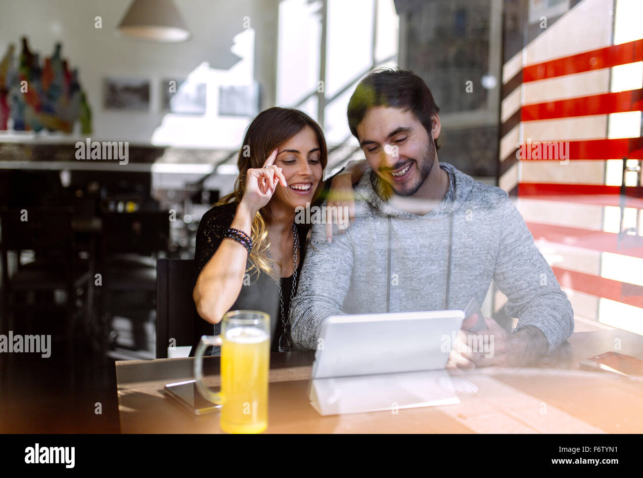 Happy young couple using digital tablet in a pub - Stock Image