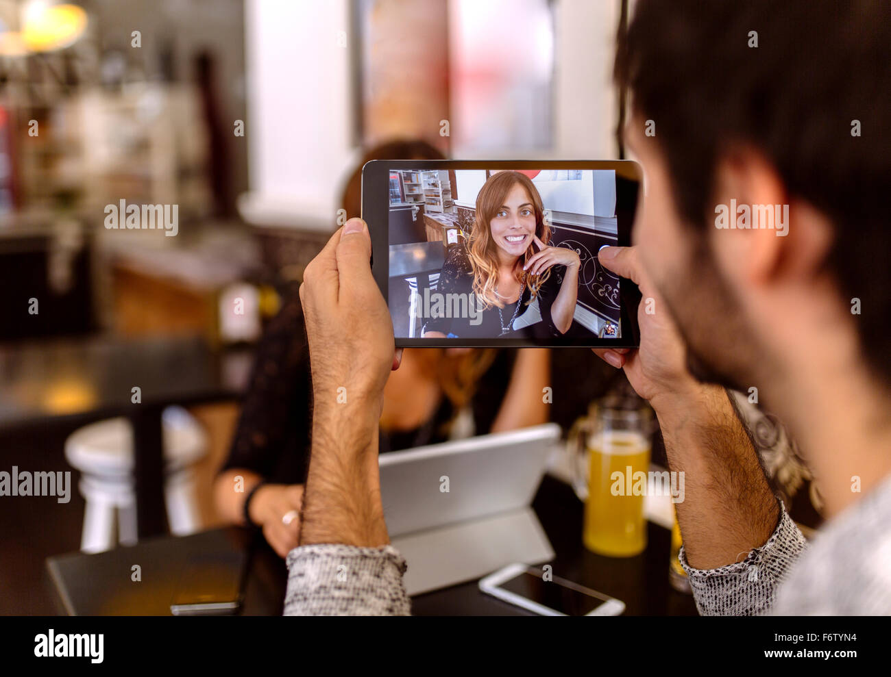 Young man taking photography of  his girlfriend with digital tablet - Stock Image