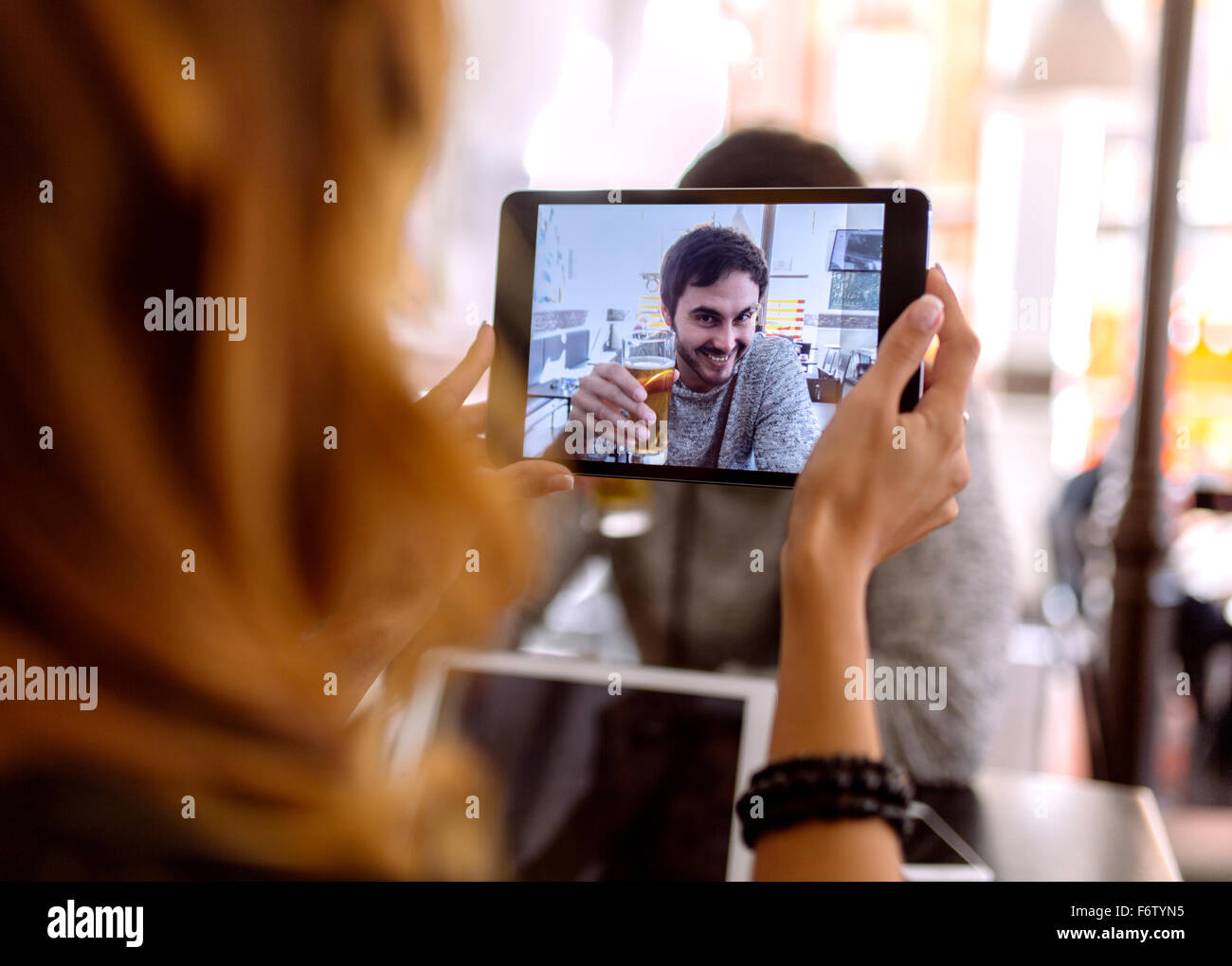 Young woman taking photography of  her boyfriend with digital tablet - Stock Image