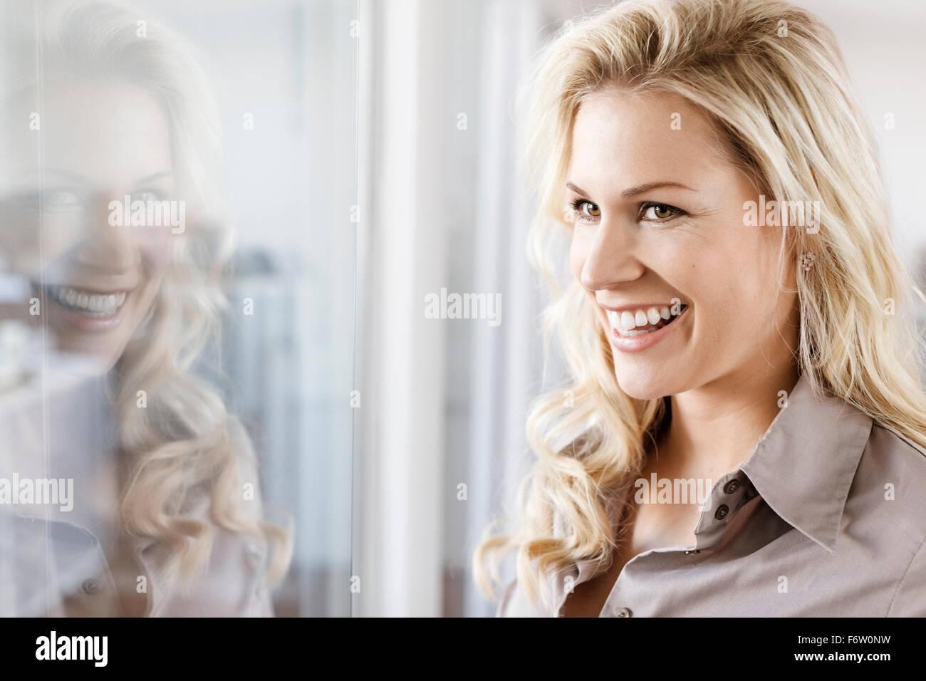Smiling woman looking through glass pane - Stock Image