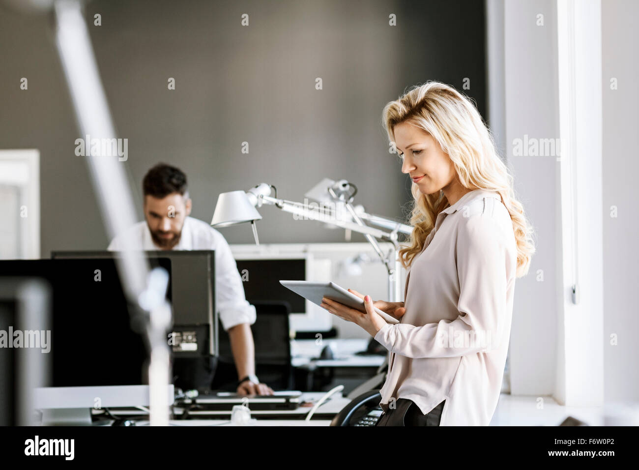 Two colleagues in office with digital tablet and computer - Stock Image