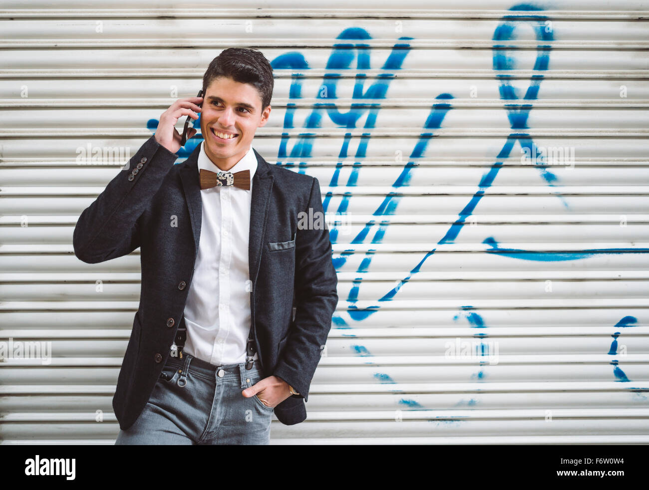 Young man on the phone wearing jacket and a wooden bow tie - Stock Image