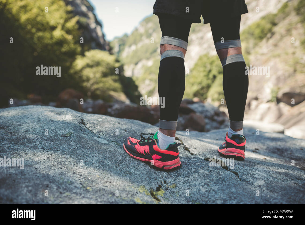 Ultra runner in mountains standing on rock - Stock Image