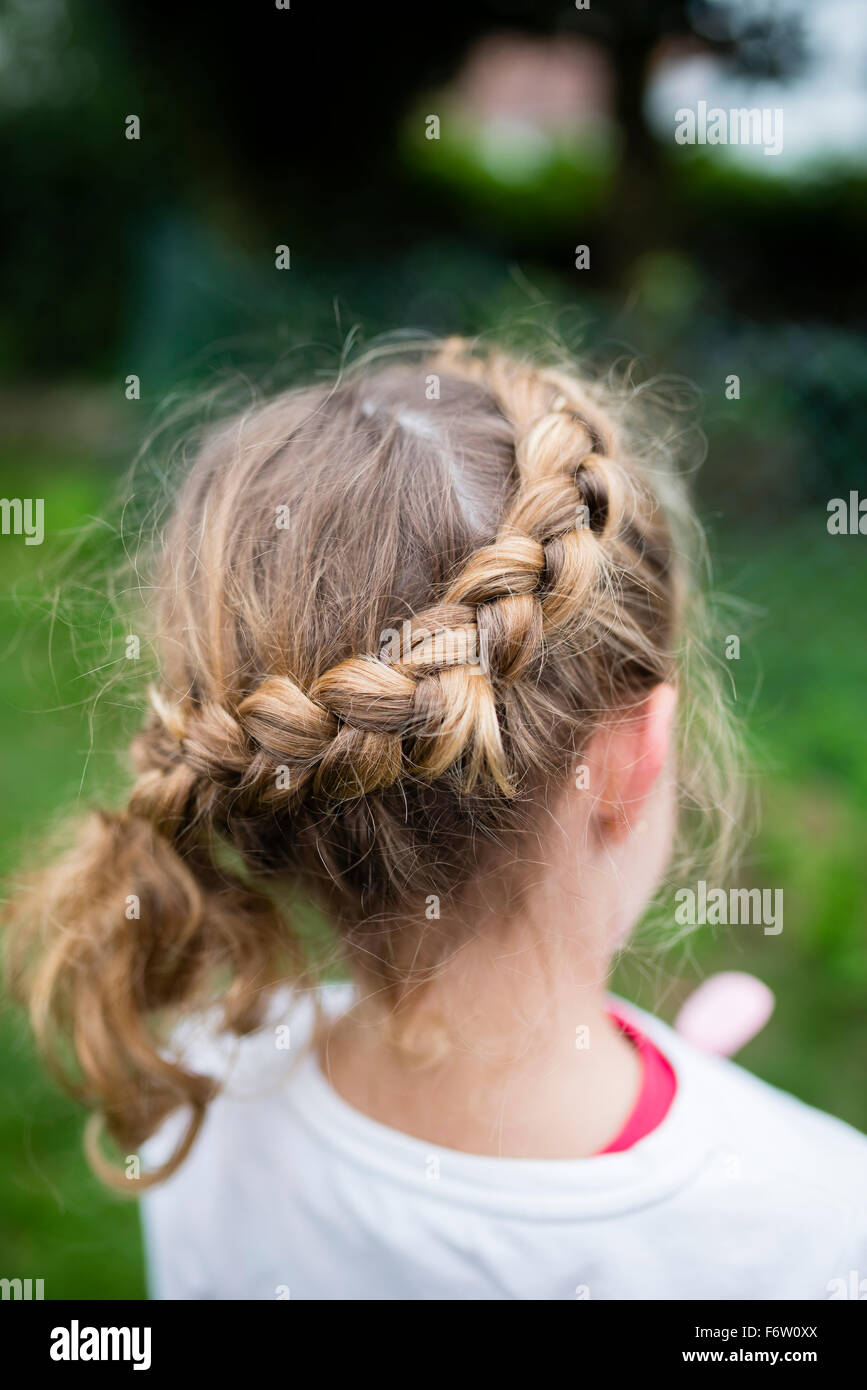 Braided hair of a blond girl - Stock Image