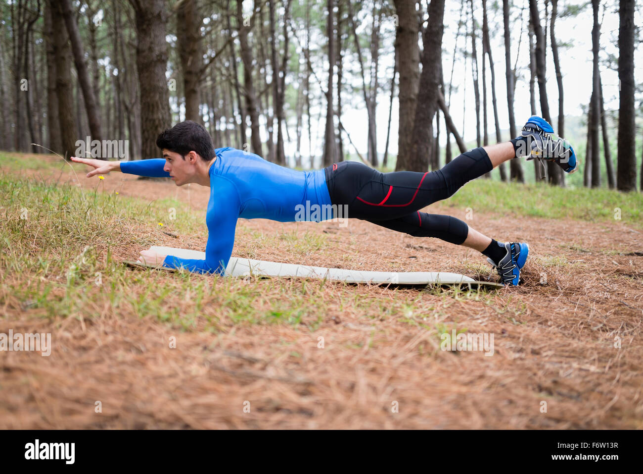 Athlete exercising planks in forest - Stock Image