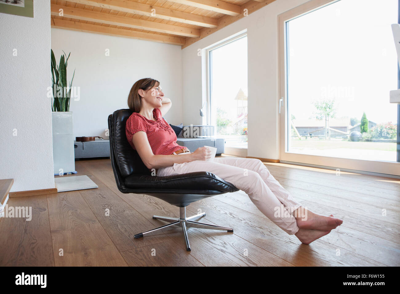 Mature woman sitting relaxed in her living room, drinking coffee ...