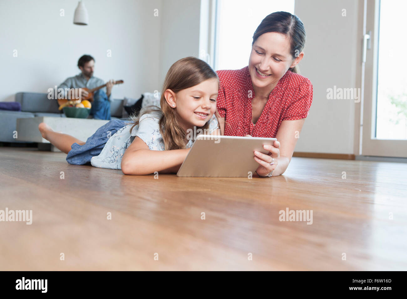 Mother and daughter lying on floor using digital tablet, father making music in background Stock Photo