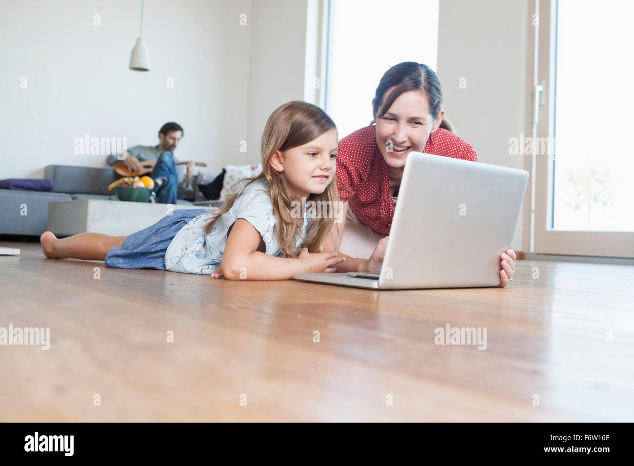 Mother and daughter lying on floor using laptop, father making music in background - Stock Image