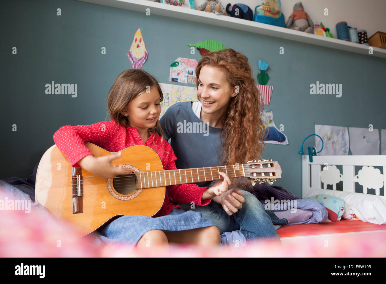 Little girl playing guitar while her mother listening - Stock Image
