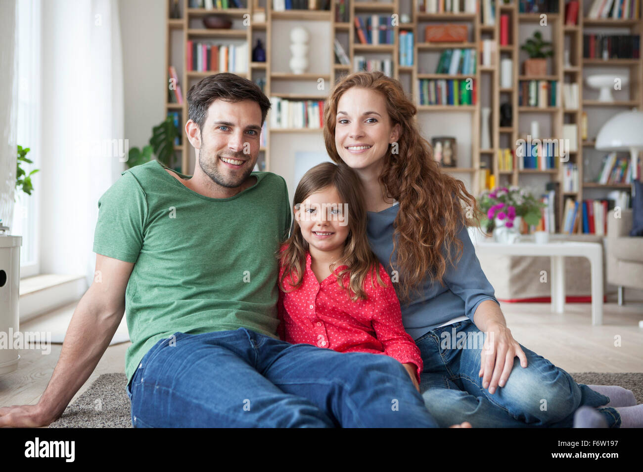 Portrait of little girl and her parents sitting together on floor in the living room - Stock Image