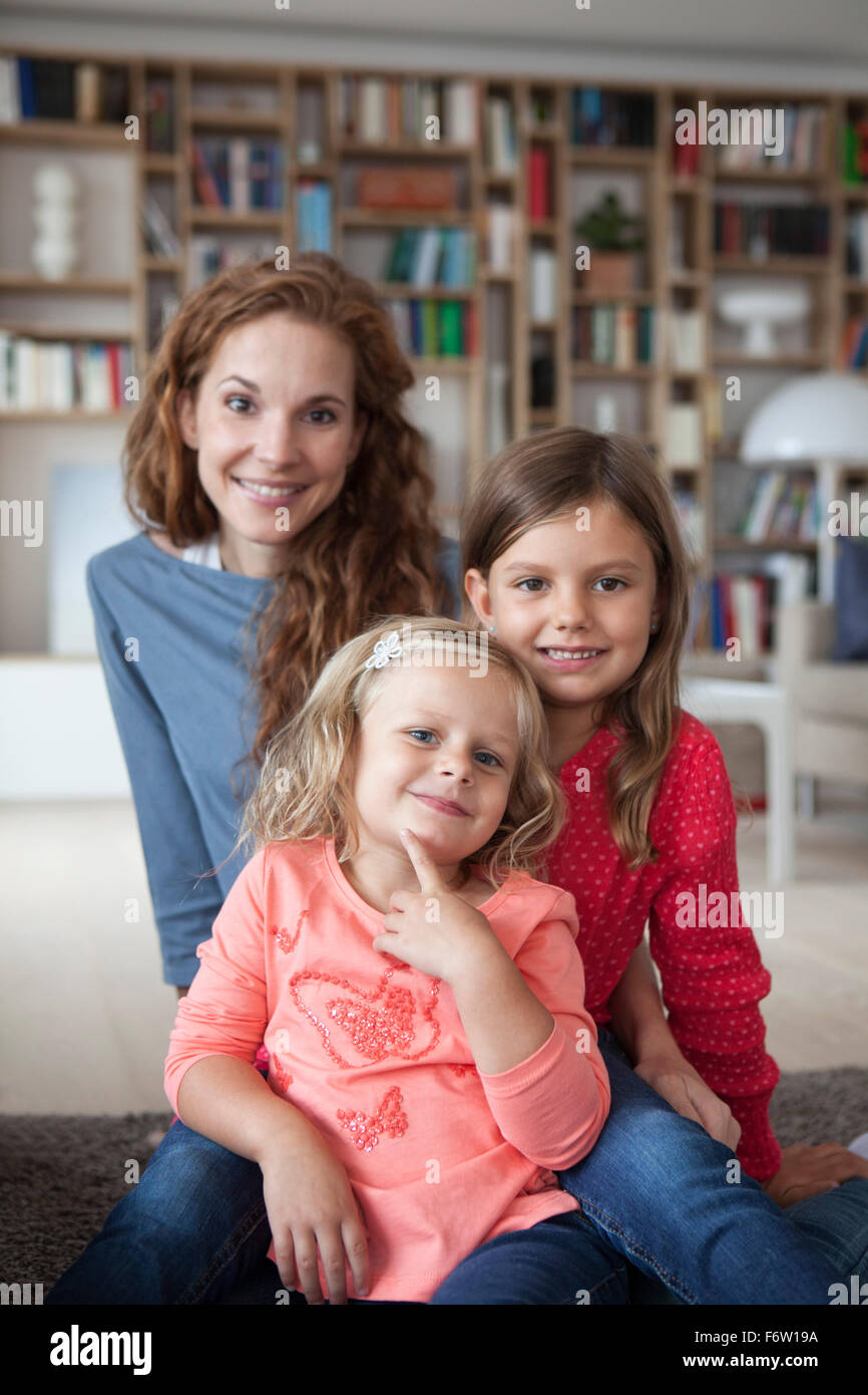 Portrait of two little sisters and her mother in the background sitting on the floor at living room - Stock Image