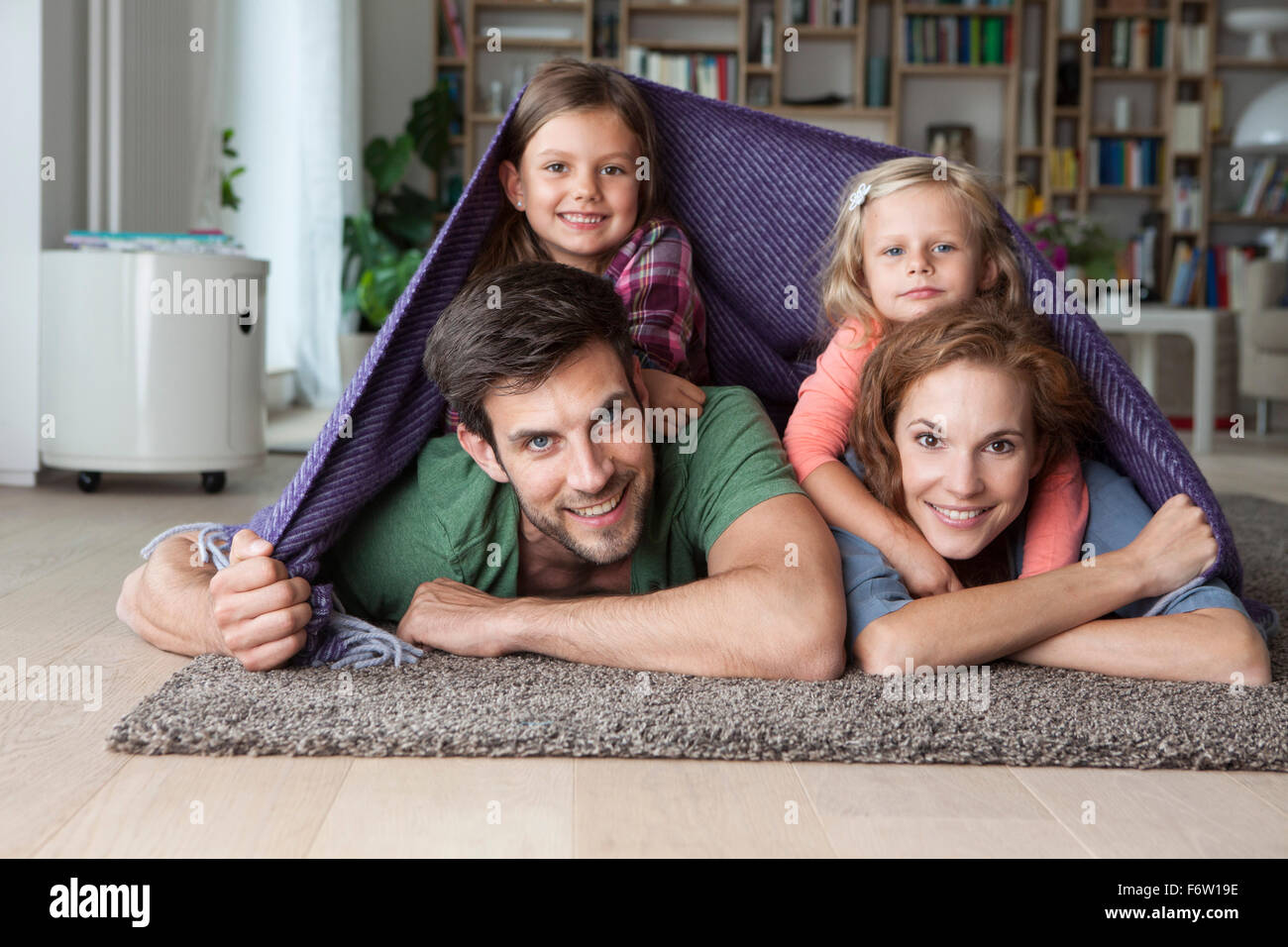 Portrait of couple with her little daughters lying together on the floor of the living room covered by a blanket Stock Photo
