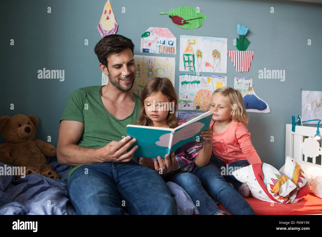 Father and his little daughters sitting together on bed in children's room reading a book Stock Photo
