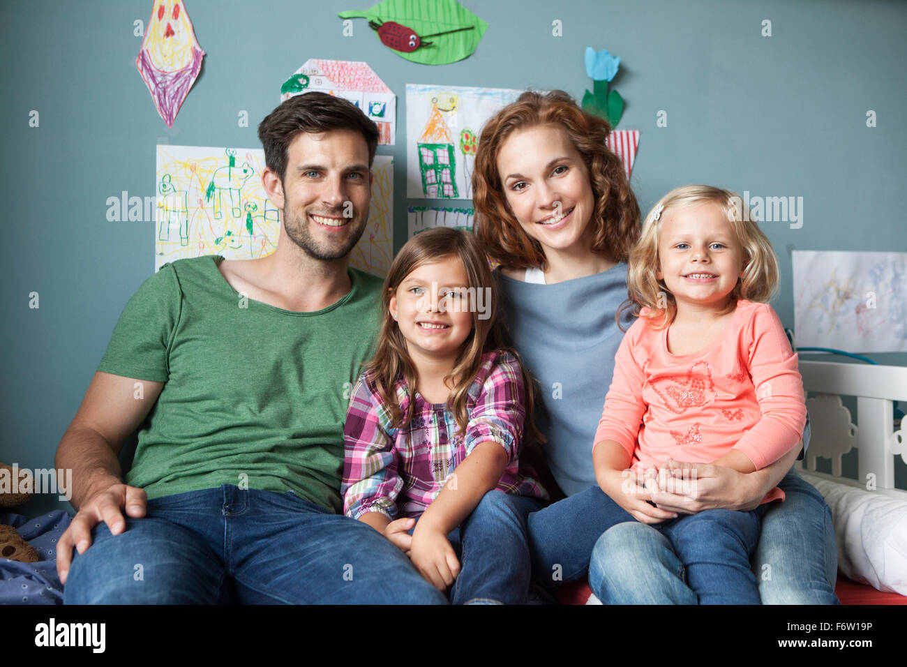 Family picture of couple with her little daughters sitting together on bed in children's room Stock Photo