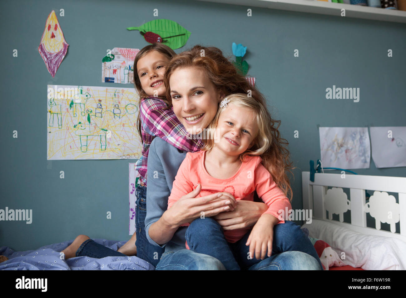 Portrait of woman with her little daughters in children's room - Stock Image