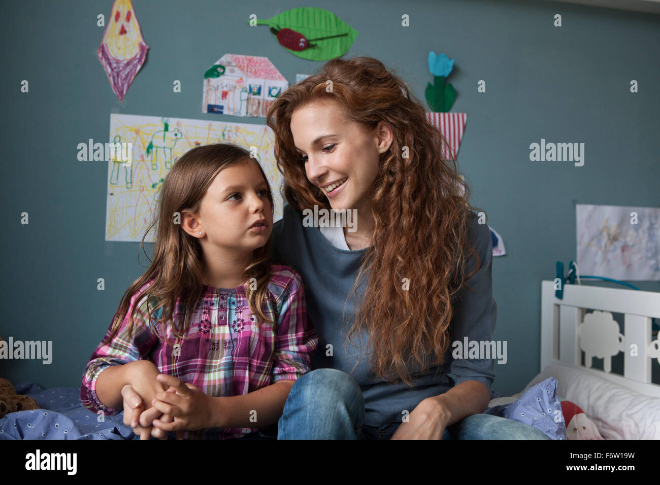 Portrait of woman with her little daughter in children's room Stock Photo