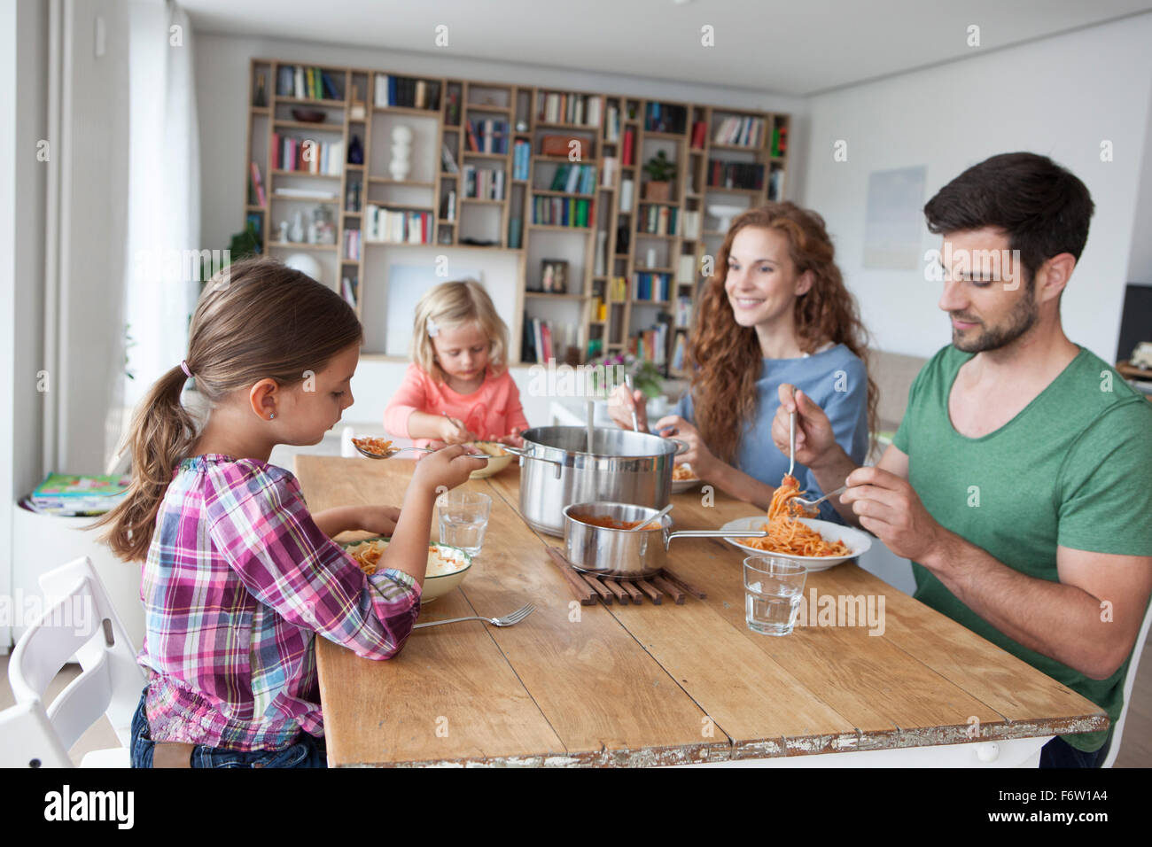 Little girl sitting at dining table with her parents and sister eating spaghetti - Stock Image