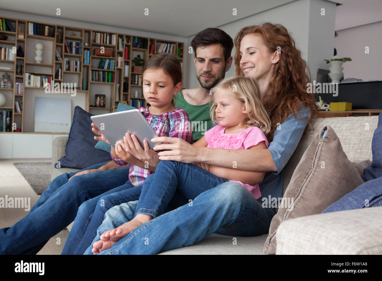 Couple sitting with their with two little daughters on couch in the living room looking at digital tablet - Stock Image