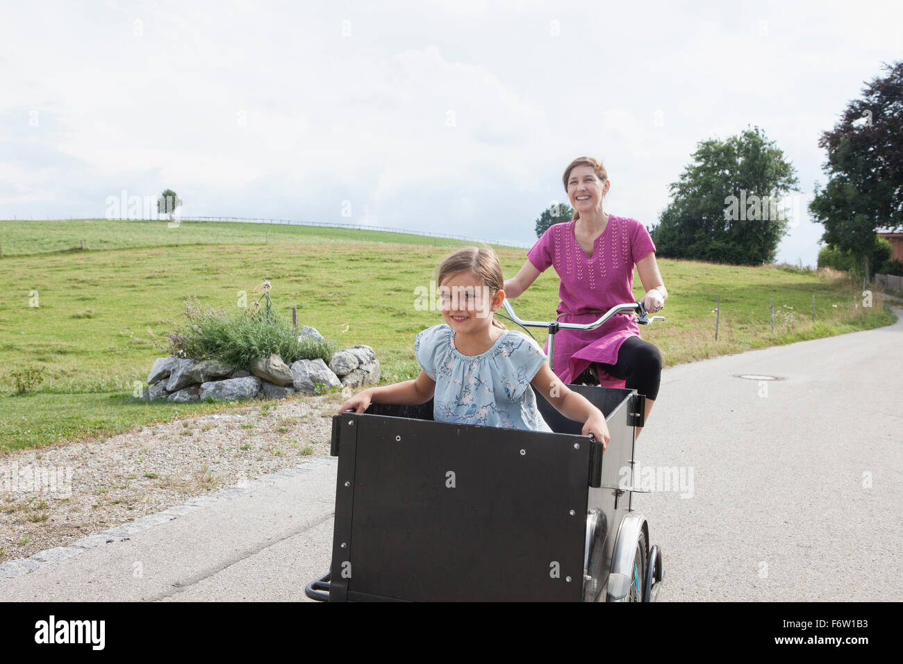 Mother riding bicycle with daughter in trailer - Stock Image