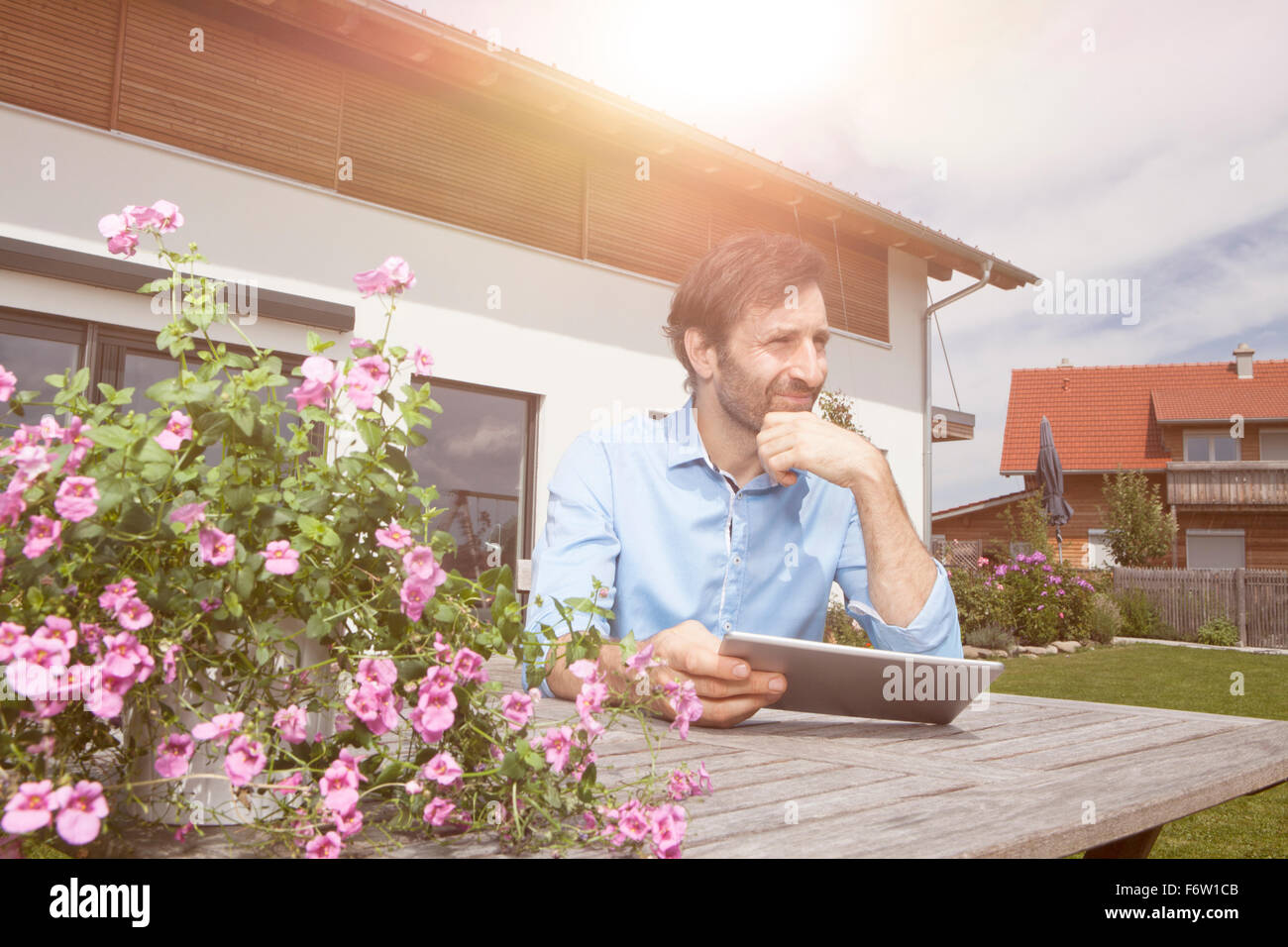 Man with digital tablet in garden - Stock Image