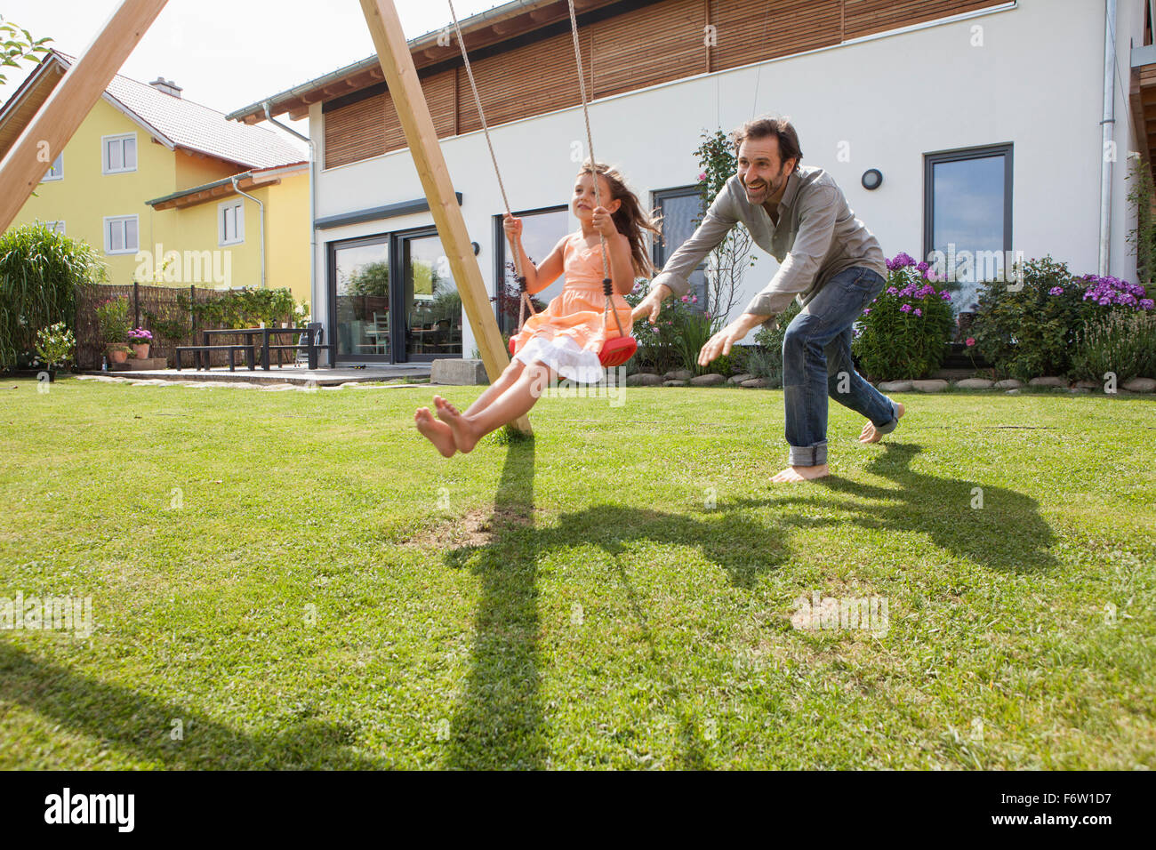 Father pushing daughter on a swing in garden Stock Photo