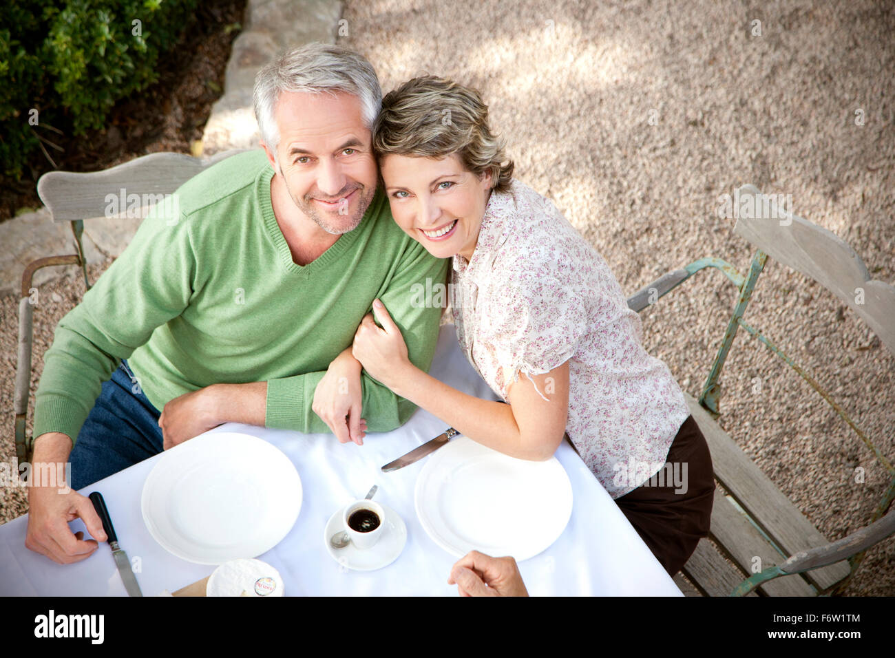 Portrait of smiling couple sitting at laid table in the garden looking up to camera - Stock Image
