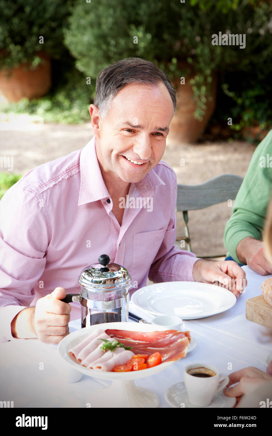 Portrait of smiling man sitting at laid table in the garden communicating with friends - Stock Image