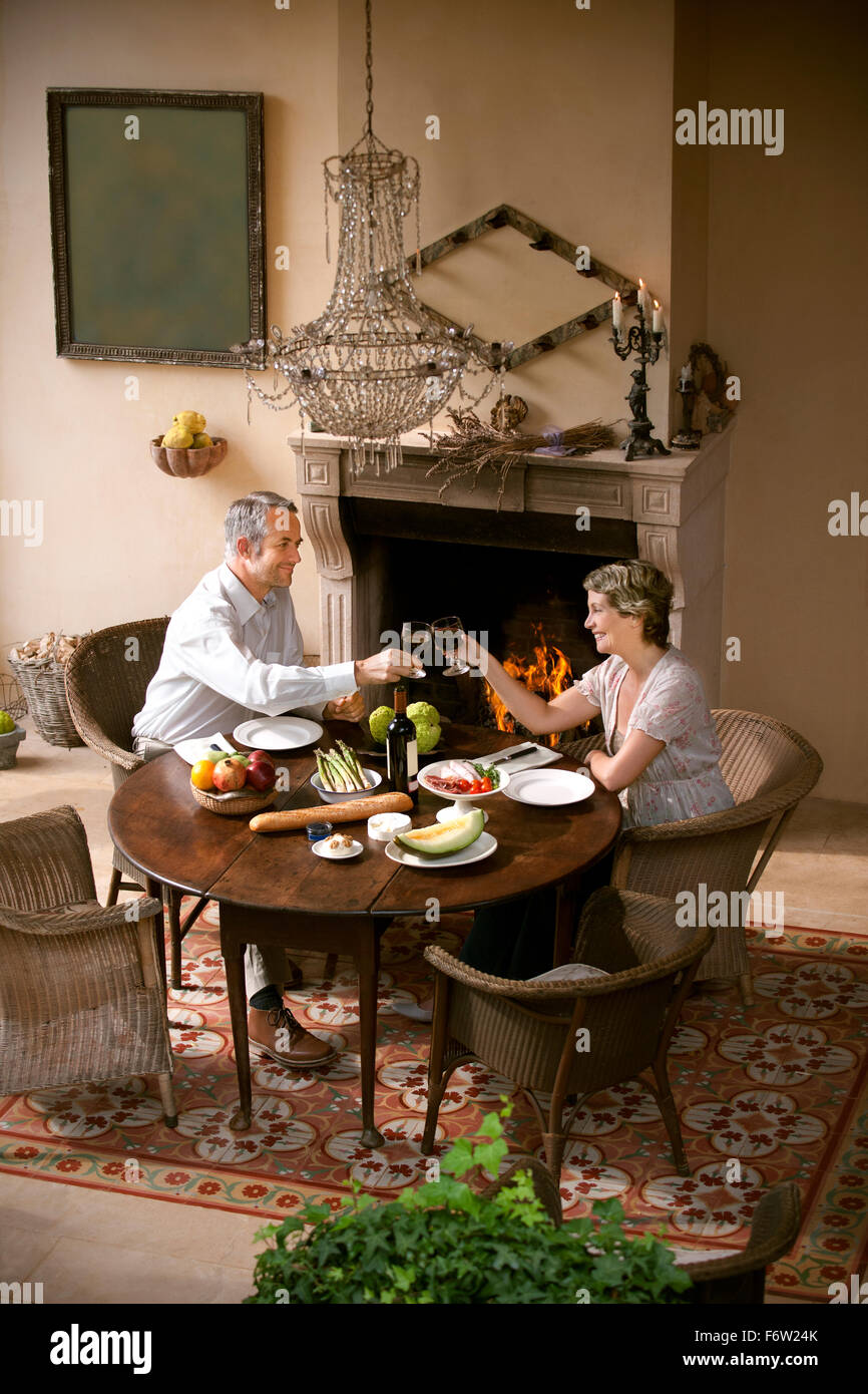 Mature couple sitting at laid table toasting with red wine in front of open fire - Stock Image