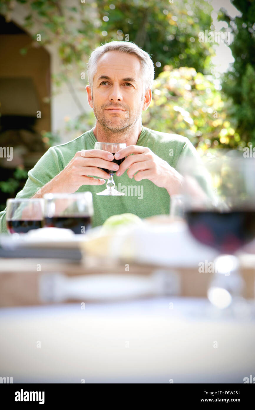 Portrait of daydreaming man sitting at laid table in the garden holding glass of red wine - Stock Image