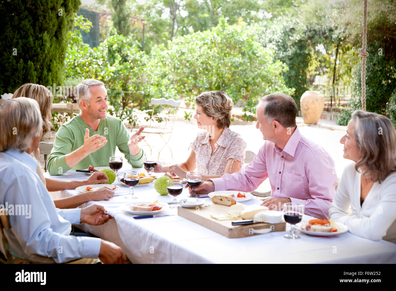 Spain, Mallorca, six friends sitting at laid table in the garden - Stock Image