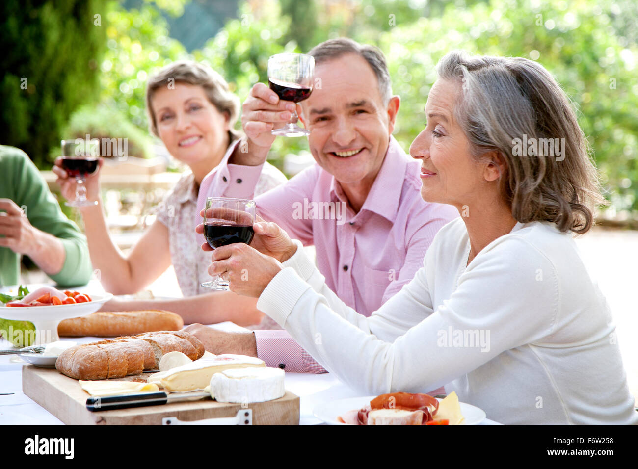 Spain, Mallorca, mature man sitting with friends at laid table in the garden toasting with red wine - Stock Image