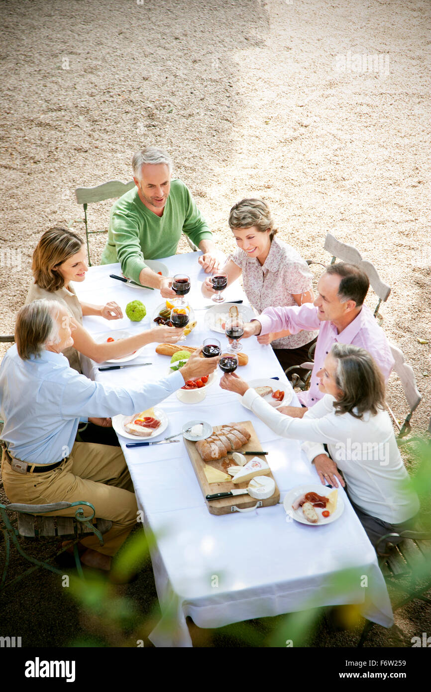 Six friends sitting at laid table in the garden toasting with red wine - Stock Image