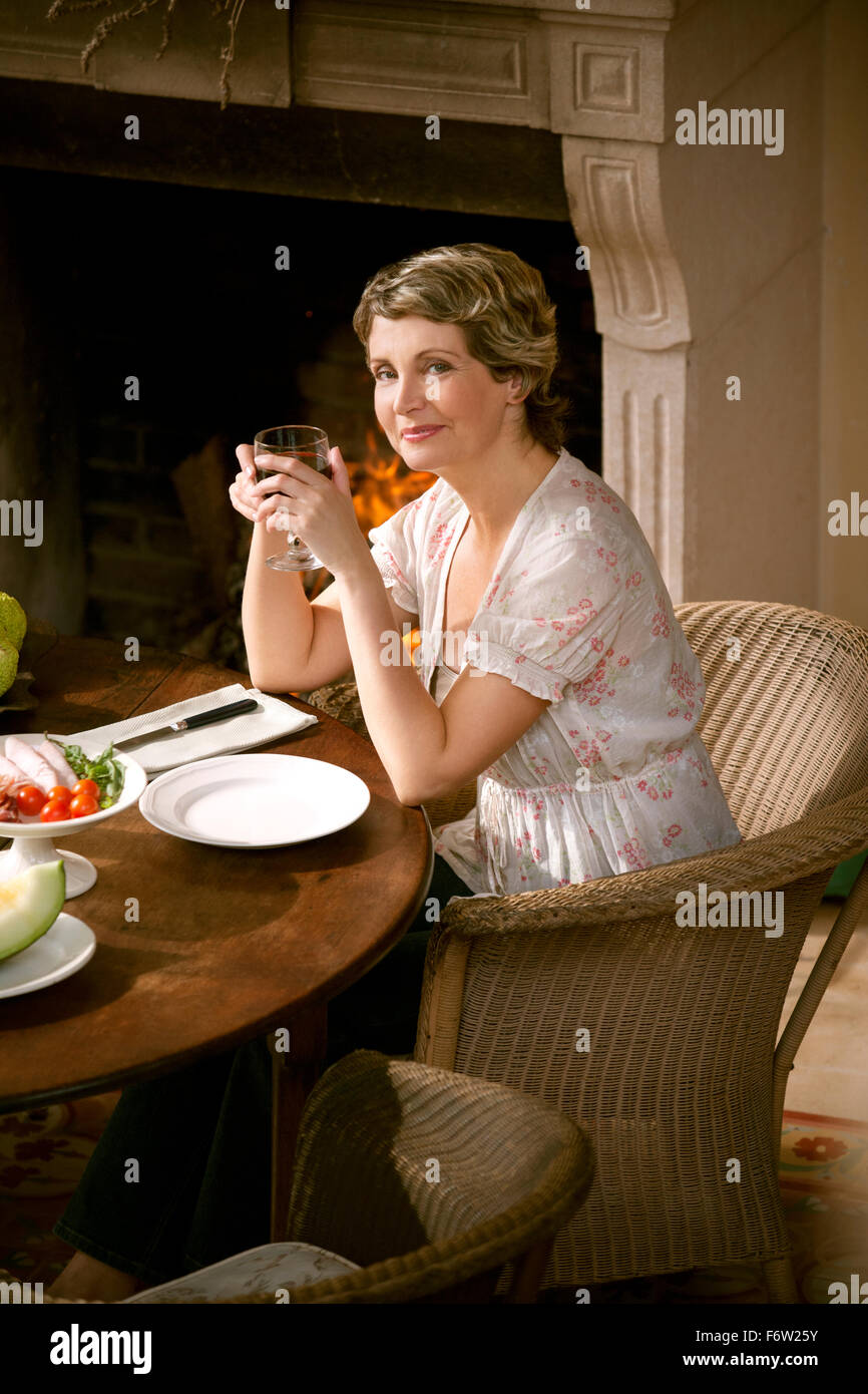 Portrait of smiling mature woman sitting at laid table holding glass of red wine - Stock Image