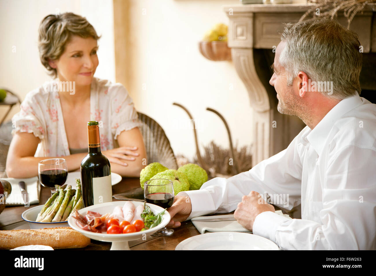 Couple sitting at laid table looking at each other - Stock Image