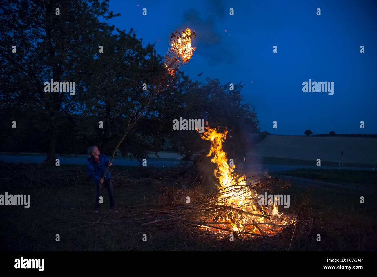 Germany, boy at camp fire on a meadow in the evening - Stock Image
