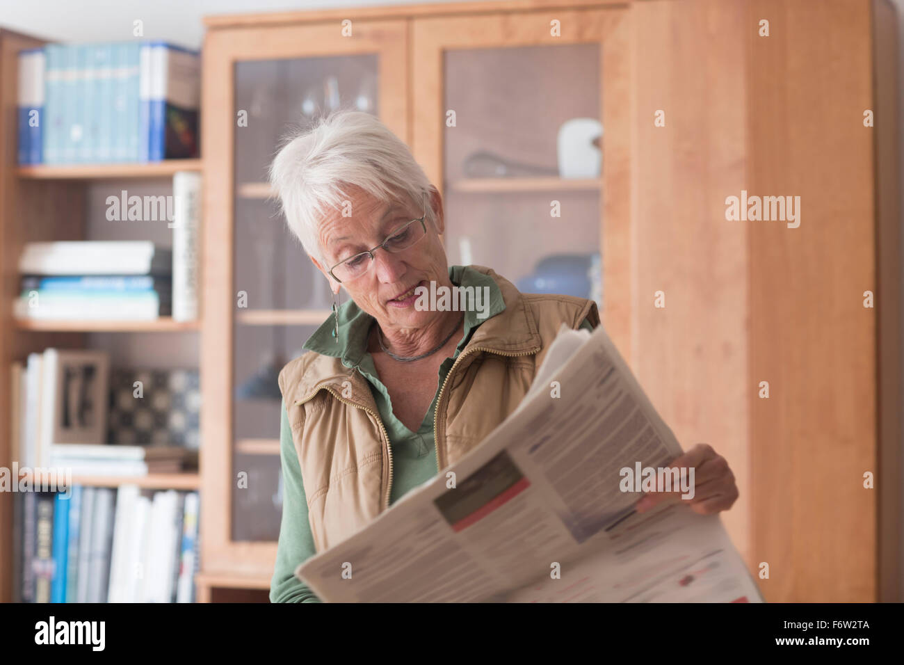 Portrait of white haired senior woman reading newspaper at home - Stock Image