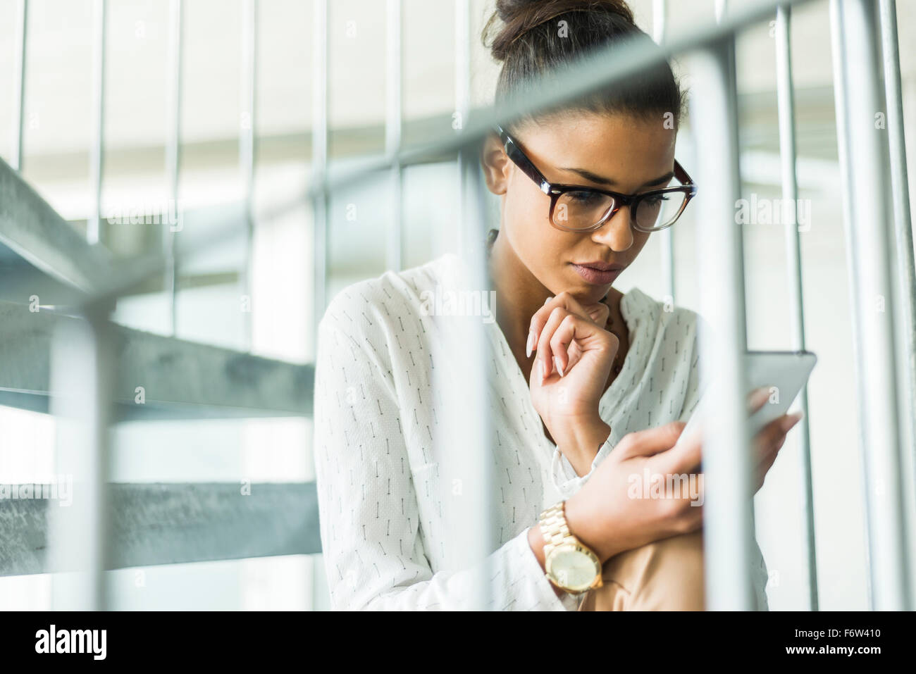 Young woman aon spiral staircase looking on cell phone - Stock Image