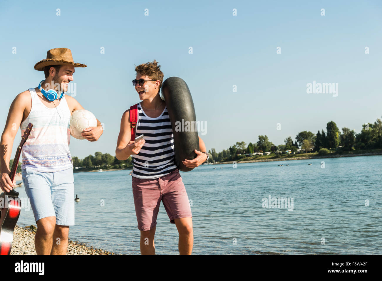 Two friends with inner tube and guitar walking at the riverside - Stock Image