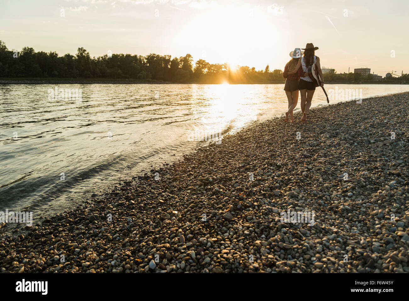 Two friends walking at the riverside at sunset - Stock Image