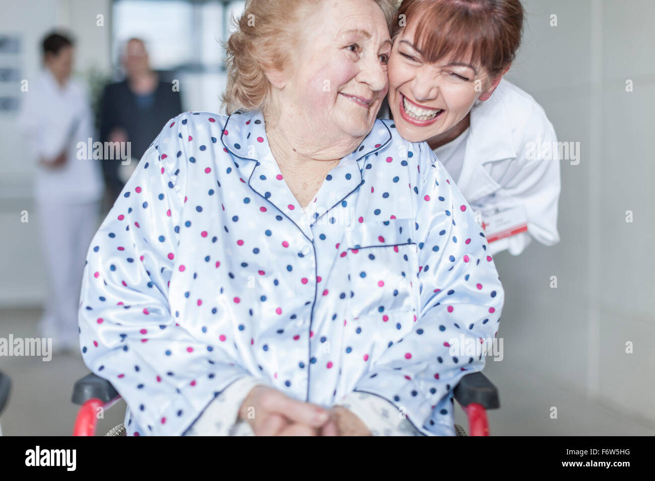 Doctor caring for elderly patient in wheelchair - Stock Image