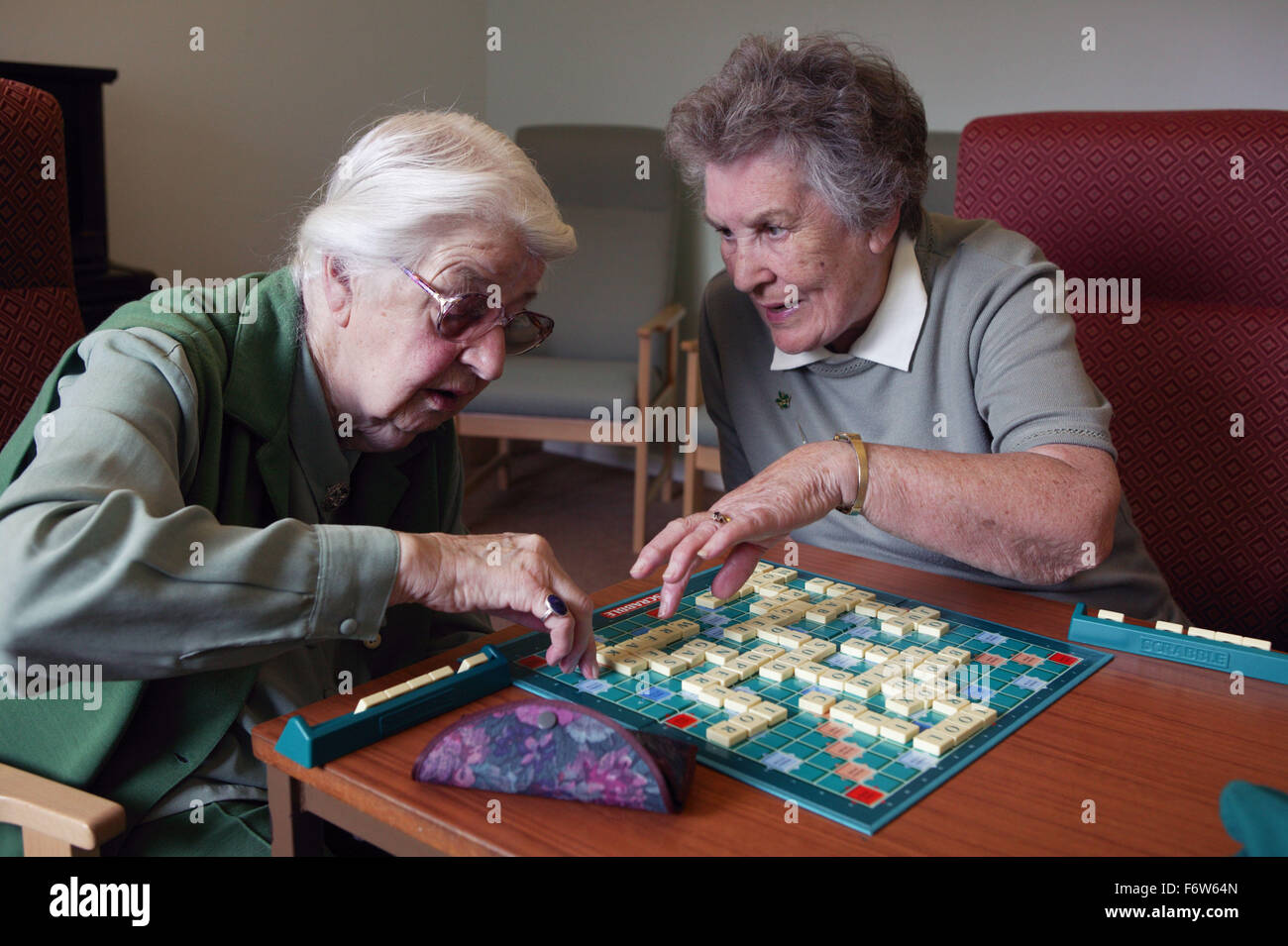 Two elderly women playing game of scrabble at day centre, - Stock Image