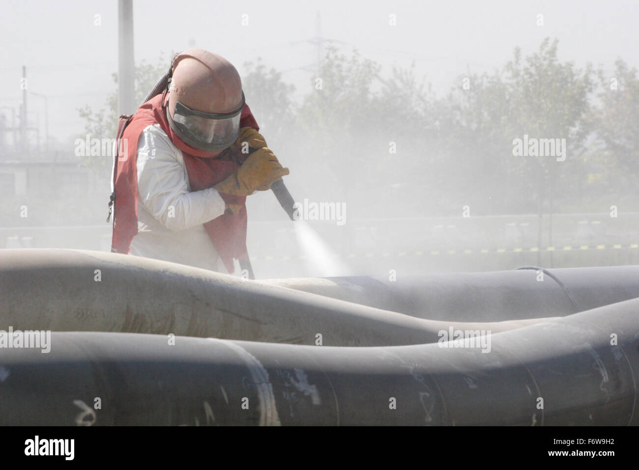 A worker uses high-pressure grit blasting to clean petrochemical pipes - Stock Image