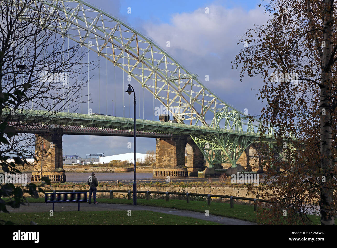 A man looks at the Silver Jubilee bridge across the River Mersey in Runcorn, Cheshire, UK - Stock Image